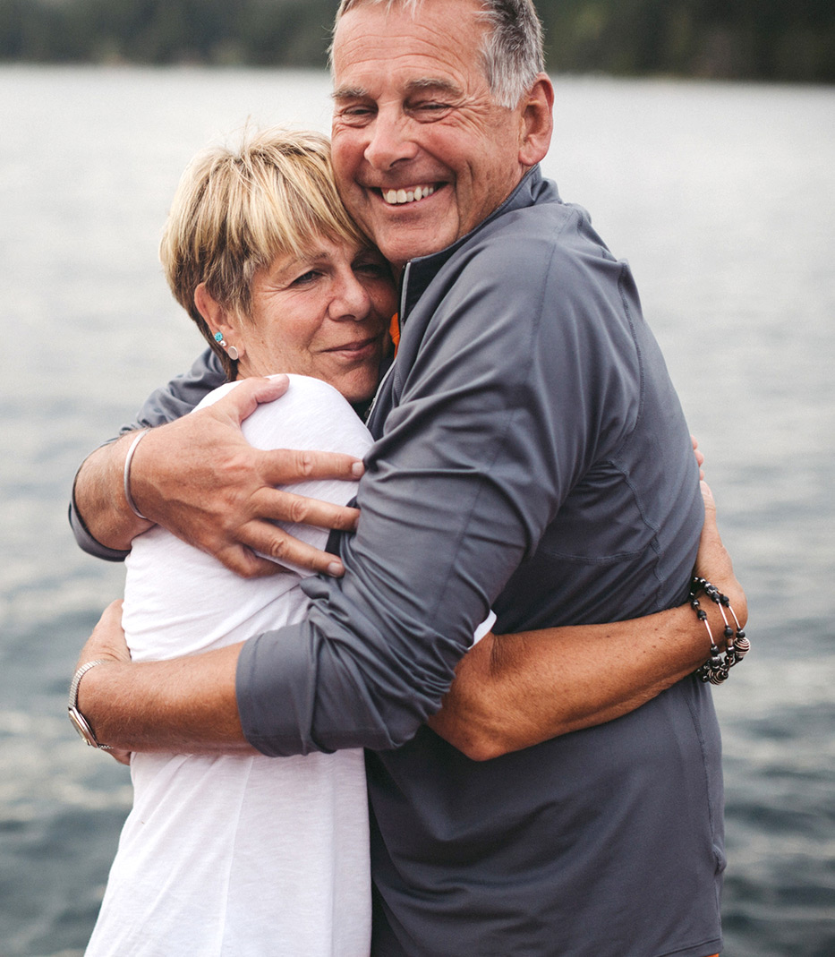 older couple hugging by lake