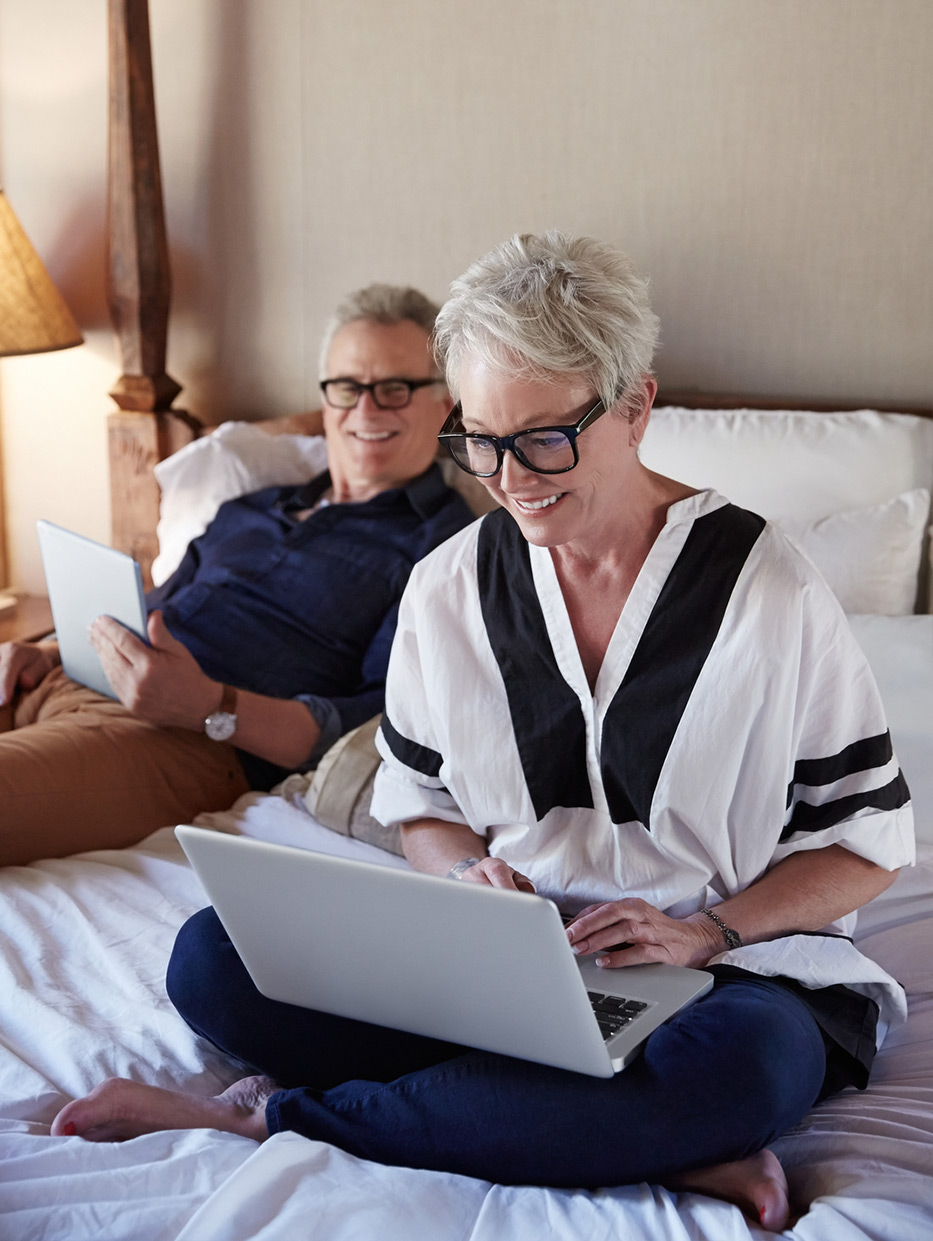 older couple in bed looking at laptops