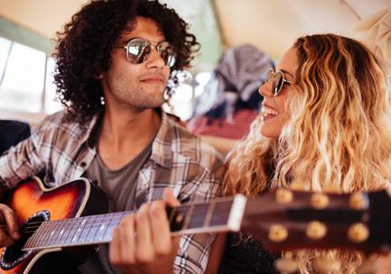 Man playing guitar next to woman