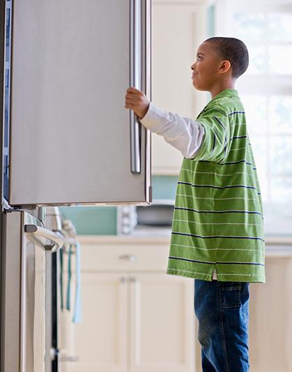 Boy opening refrigerator