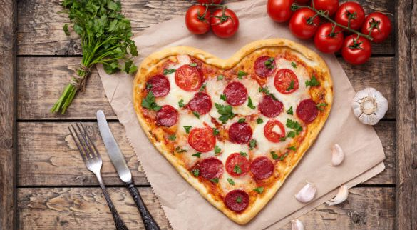 Heart shaped pizza for Valentines day with pepperoni, mozzarella, tomatoes