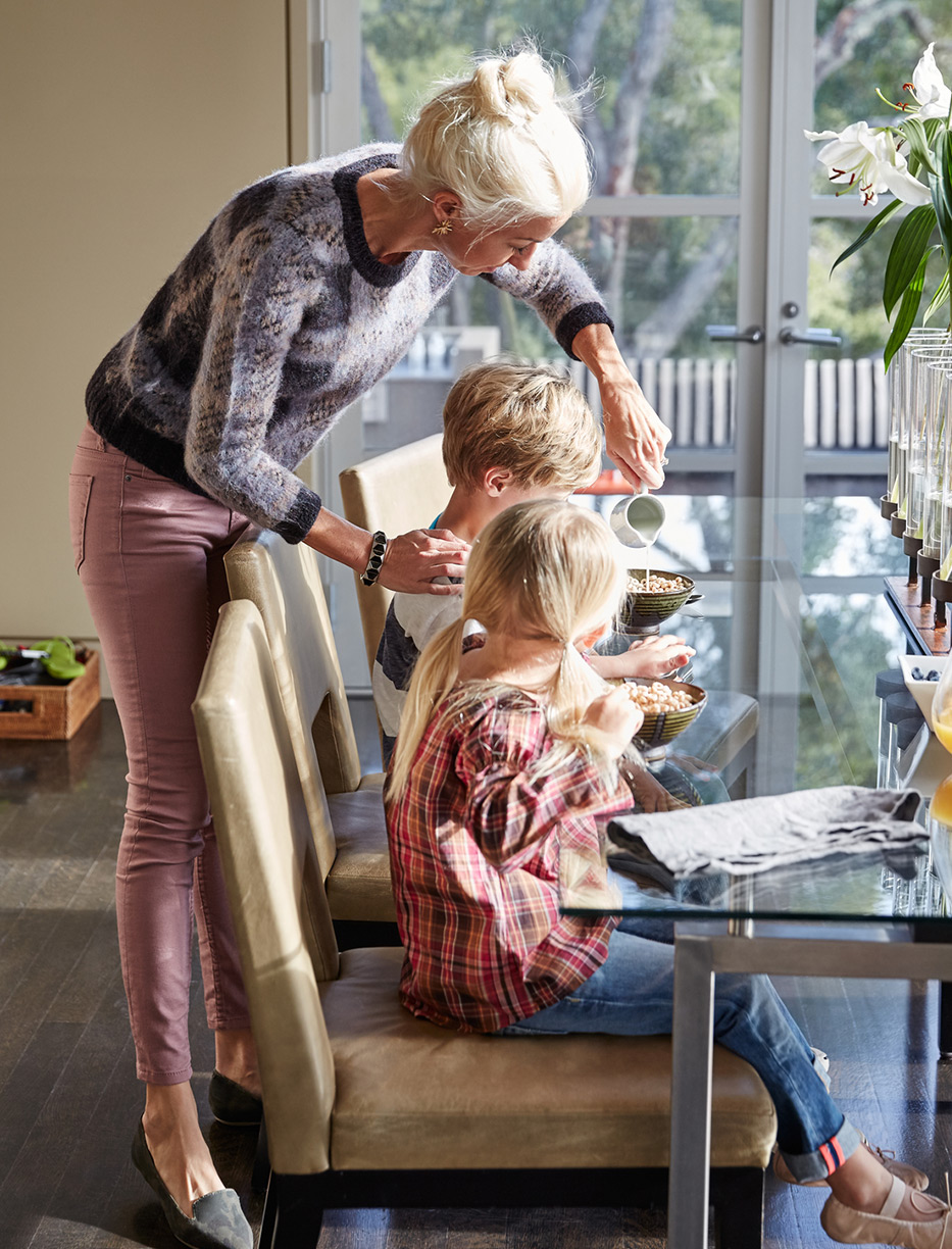 two kids sitting at table while mom gives them cereal