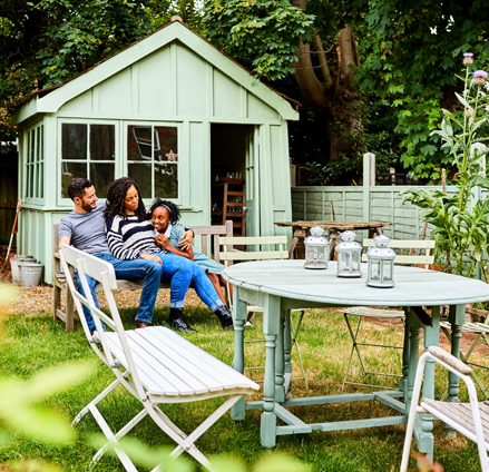 Family sitting around table in backyard