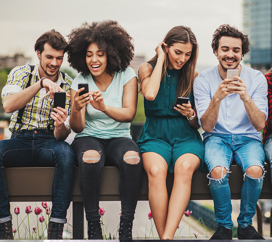 group of friends sitting on ledge on phone
