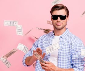 Portrait of his he nice cool trendy content attractive handsome candid guy wearing checked shirt throwing money flying in air party wealth isolated over pink pastel background