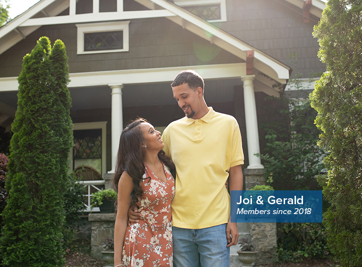 Georgia's Own members Joi and Gerald smiling at each other in front of a craftsman-style house in Decatur, Georgia